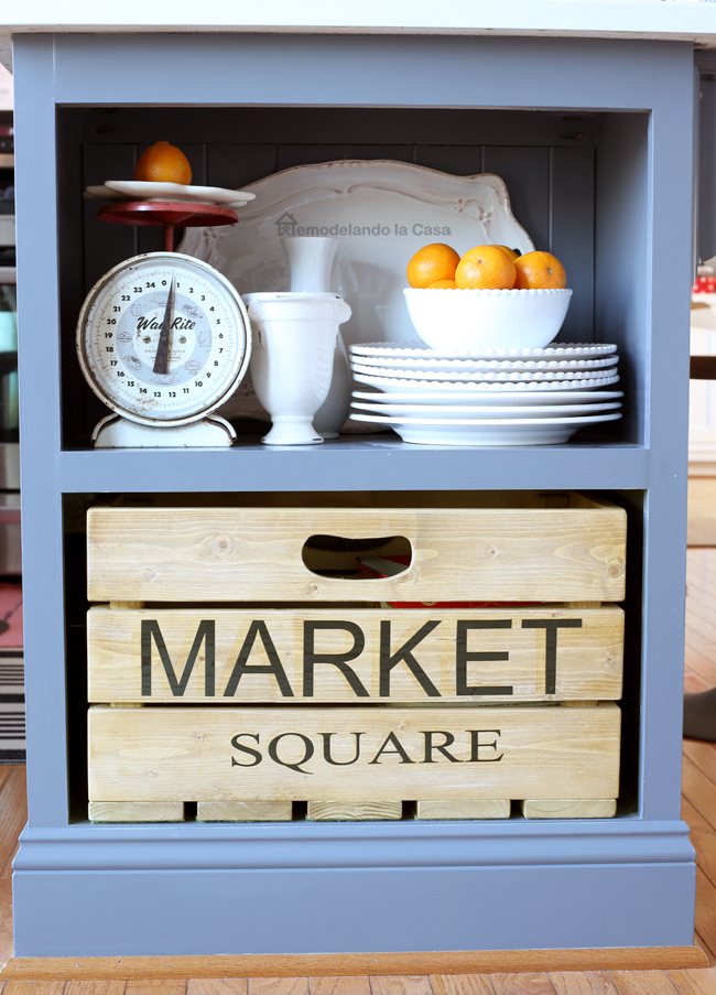grey kitchen island with market square wooden crate, vintage scale and white dishes.