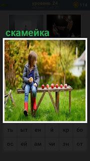 на скамейке сидит девочка и рядом в ряд сложены яблоки