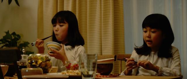 Las hermanas de Ichigo cenan dos cuencos que presuponemos serán sopa de Miso y arroz con palillos negros