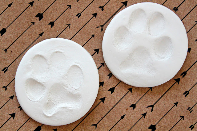 Dog paw print impressions in round pieces of white air dry clay