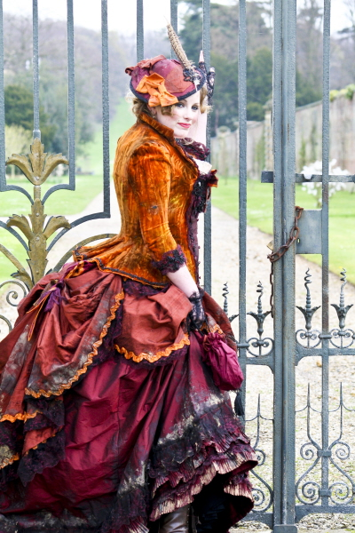 Woman wearing Victorian skirt, jacket and hat in warm colors (orange, maroon, red, purple) as part of a Victorian Prostitute costume