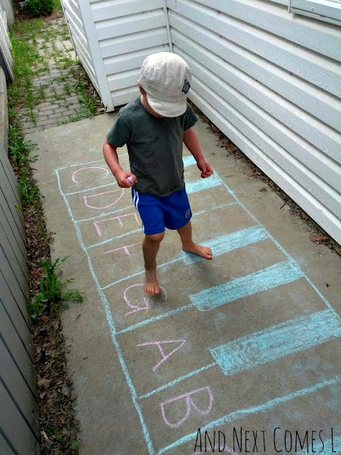 Child standing on a chalk piano with letters on it