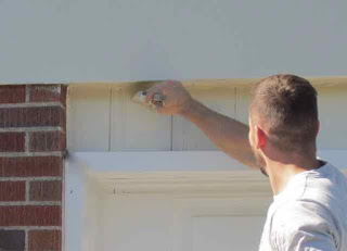 Painter painting a house.