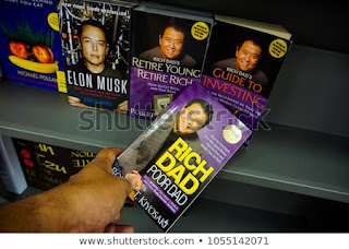 Rich dad poor dad book holding at hand