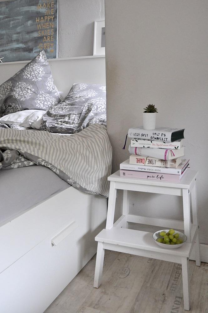 schlafzimmer einrichten hocker buecher bett