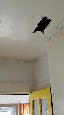 kitchen ceiling with cracked plaster and a hole