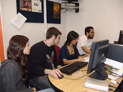 Estudiantes universitarios buscando información en una mesa de estudio con apuntes y computadoras
