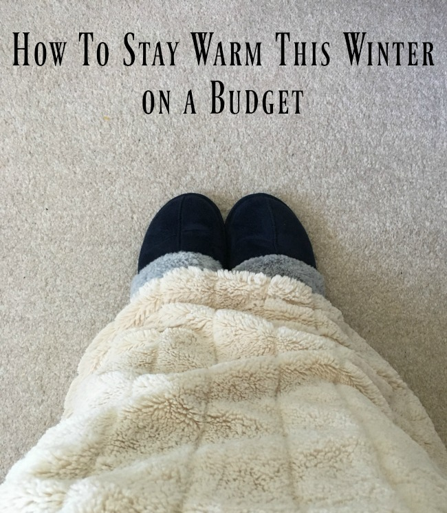 How-To-Stay-Warm-This-Winter-on-a-Budget-text-over-image-of-feet-in-slippers-and-legs-covered-with-faux-fur-throw