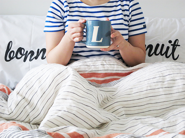 L blue monogram mug, black/white bonne nuite pillowcases, West Elm striped linen duvet cover