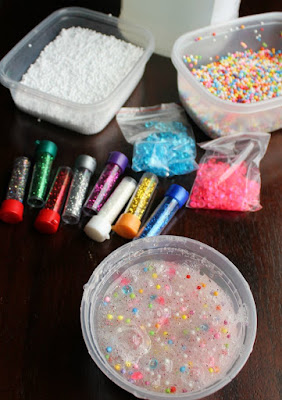 tub of slime next to tubes of glitter, plastic beads, foam balls and gallon of clear glue