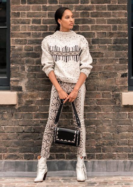 Девушка в узких брюках со змеиным принтом и в свитере