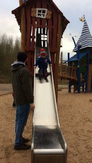 Little boy a slide being watched by his Daddy