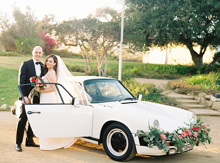 Bride and Groom with white vintage car decorated with florals and greenery | Photo by Matoli Keely Photography