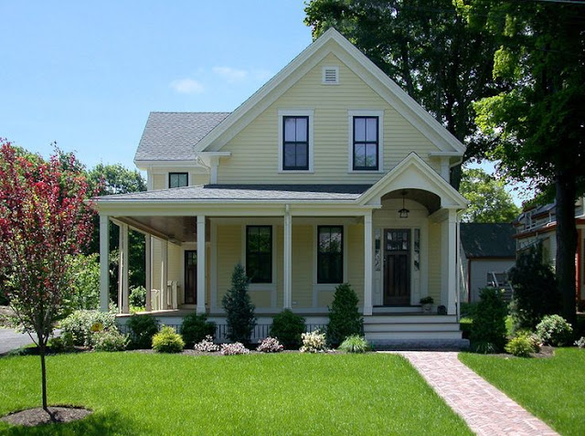 Yellow two story house with white trim and a wrap around porch.