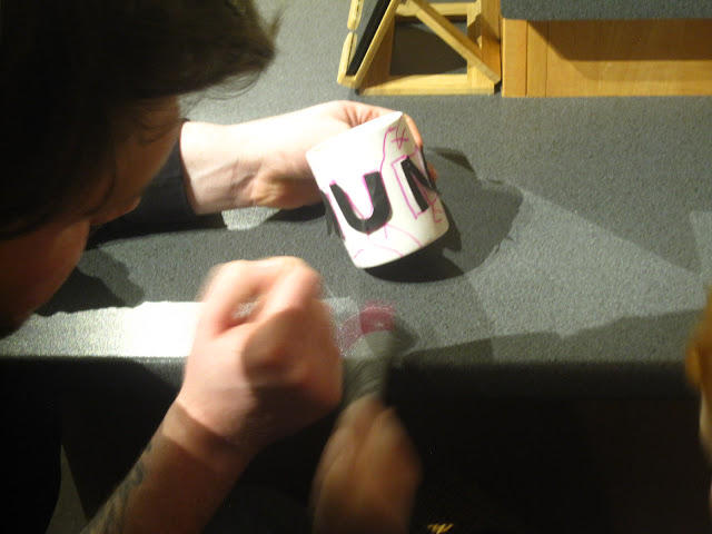 Daddy and child decorating a mug together