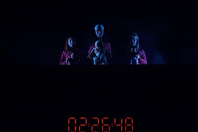 three young girls in pyjamas against a dark background, with a digital clock below
