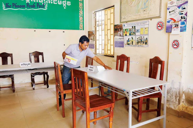 Toch Nimol, president of a registration station in Phnom Penh, sets up the office in Chamkarmon district on Tuesday. Pha Lina