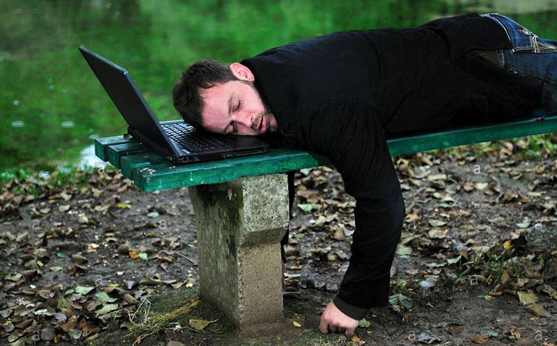 Программист спит на скамейке в парке, подложив под голову ноутбук.