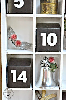 Junky DIY ornaments fill a shot glass display box to create an advent calendar