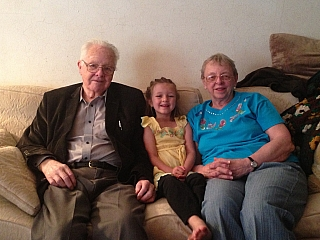Grand parents and grand daughter sitting on a couch