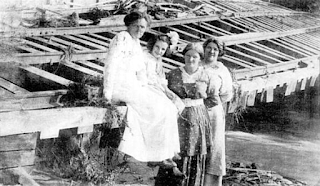 Four ladies are sitting on trolley tracks, at Four Mile Creek Amusement Park, that were damaged by the storm that precipitated the Mill Creek flood of August 3, 1915