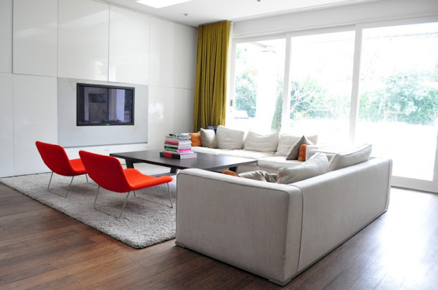 living room with white sectional sofa with orange accent pillows, two red chairs, wood floor, a gray shag rug, large windows and green floor length curtains
