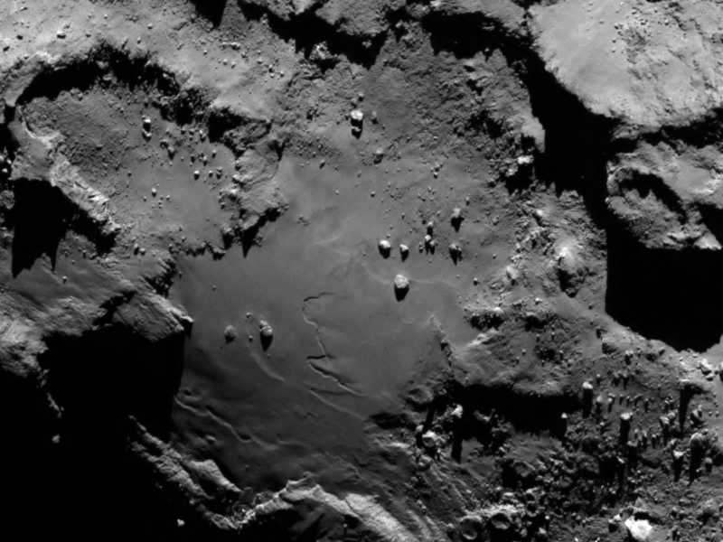 Rosetta's Target Up Close Rosetta's Target Up Close  Close up detail focusing on a smooth region on the 'base' of the 'body' section of comet 67P/Churyumov-Gerasimenko. The image was taken by Rosetta's Onboard Scientific Imaging System (OSIRIS) on August 6, 2014. The image clearly shows a range of features, including boulders, craters and steep cliffs. The image was taken from a distance of 80 miles (130 kilometers) and the image resolution is 8 feet (2.4 meters) per pixel.  The three U.S. instruments aboard the spacecraft are the Microwave Instrument for Rosetta Orbiter (MIRO), an ultraviolet spectrometer called Alice, and the Ion and Electron Sensor (IES). They are part of a suite of 11 science instruments aboard the Rosetta orbiter.  MIRO is designed to provide data on how gas and dust leave the surface of the nucleus to form the coma and tail that gives comets their intrinsic beauty. Studying the surface temperature and evolution of the coma and tail provides information on how the comet evolves as it approaches and leaves the vicinity of the sun.  Alice will analyze gases in the comet's coma, which is the bright envelope of gas around the nucleus of the comet developed as a comet approaches the sun. Alice also will measure the rate at which the comet produces water, carbon monoxide and carbon dioxide. These measurements will provide valuable information about the surface composition of the nucleus.  NASA also provided part of the electronics package for the Double Focusing Mass Spectrometer, which is part of the Swiss-built Rosetta Orbiter Spectrometer for Ion and Neutral Analysis (ROSINA) instrument. ROSINA will be the first instrument in space with sufficient resolution to be able to distinguish between molecular nitrogen and carbon monoxide, two molecules with approximately the same mass. Clear identification of nitrogen will help scientists understand conditions at the time the solar system was formed.  U.S. scientists are partnering on several non-U.S. instruments and are involved in seven of the mission's 21 instrument collaborations. NASA's Deep Space Network is supporting ESA's Ground Station Network for spacecraft tracking and navigation.  Launched in March 2004, Rosetta was reactivated in January 2014 after a record 957 days in hibernation. Composed of an orbiter and lander, Rosetta's objectives upon arrival at comet 67P/Churyumov-Gerasimenko in August are to study the celestial object up close in unprecedented detail, prepare for landing a probe on the comet's nucleus in November, and track its changes as it sweeps past the sun.  Comets are time capsules containing primitive material left over from the epoch when the sun and its planets formed. Rosetta's lander will obtain the first images taken from a comet's surface and will provide the first analysis of a comet's composition by drilling into the surface. Rosetta also will be the first spacecraft to witness at close proximity how a comet changes as it is subjected to the increasing intensity of the sun's radiation. Observations will help scientists learn more about the origin and evolution of our solar system and the role comets may have played in seeding Earth with water, and perhaps even life.  Image Credit: ESA/Rosetta/MPS for OSIRIS Team Explanation from: http://www.nasa.gov/content/rosettas-target-up-close/
