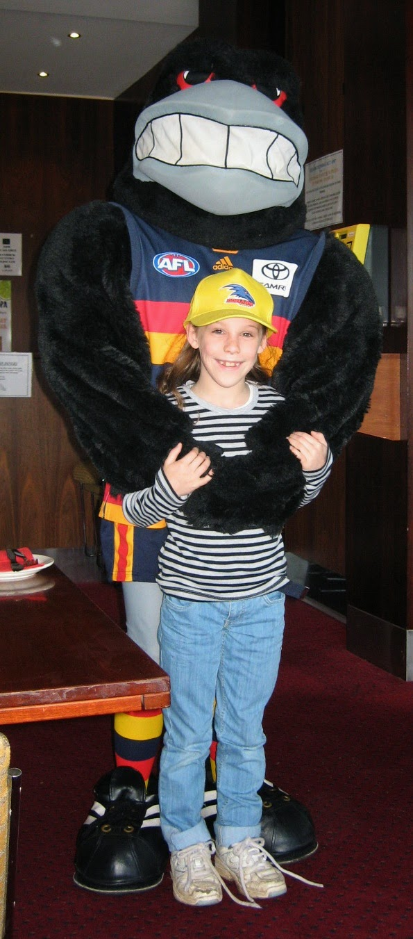 "One of my children receiving a hug from the Crows' mascot ""Claude"""