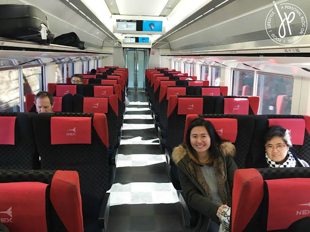 train seats, two ladies smiling, luggage on overhead rack