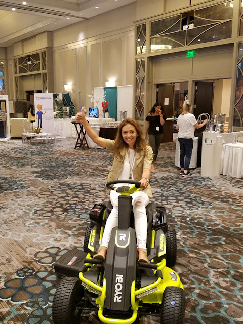 Cristina Garay riding the Ryobi Electric lawn mower during Haven conference