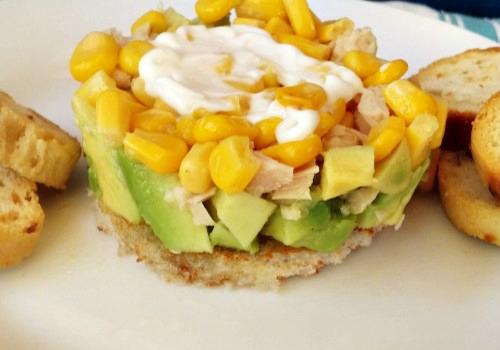 Una ensalada de colores verde (aguacate) y amarillo (maíz)