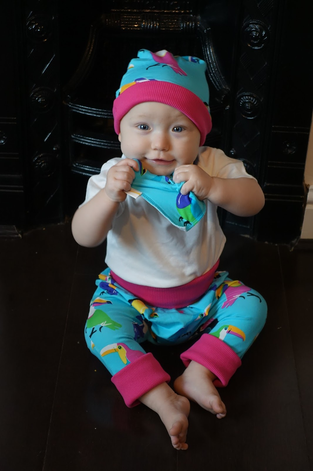 A baby wearing the Funky Toucan Funky Toucan print and pulling at the bib