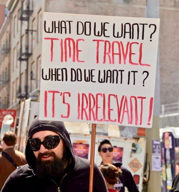 Protest sign. What do we want? Time Travel. When do we want it? It's irrelevant. Time Travel. marchmatron.com