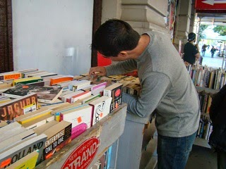 A young man borrowing a book from the library.
