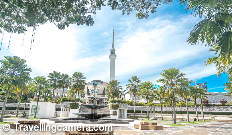 The minaret you see in above photograph is part of the National Mosque in Kuala Lumpur and is visible from almost all sides of the mosque. This is probably the highest structure in the mosque. In above photograph you also see some fountains and trees. This is what you see from the bus parking area. Most of the tourist buses drop people near this fountain and then people need to walk up to the mosque which is very close. You can take the shoes till the entrance of main building and there are arrangements to keep shoes in safe state.