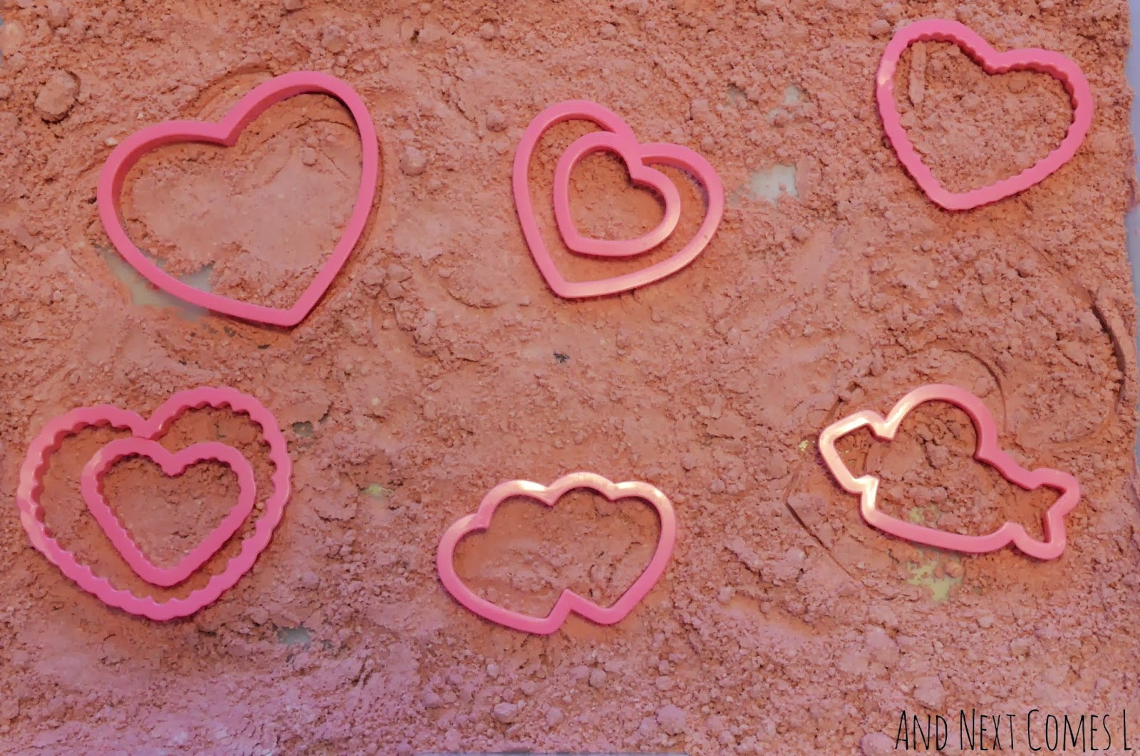Cinnamon heart cloud dough and heart cookie cutters for Valentine's Day sensory play from And Next Comes L