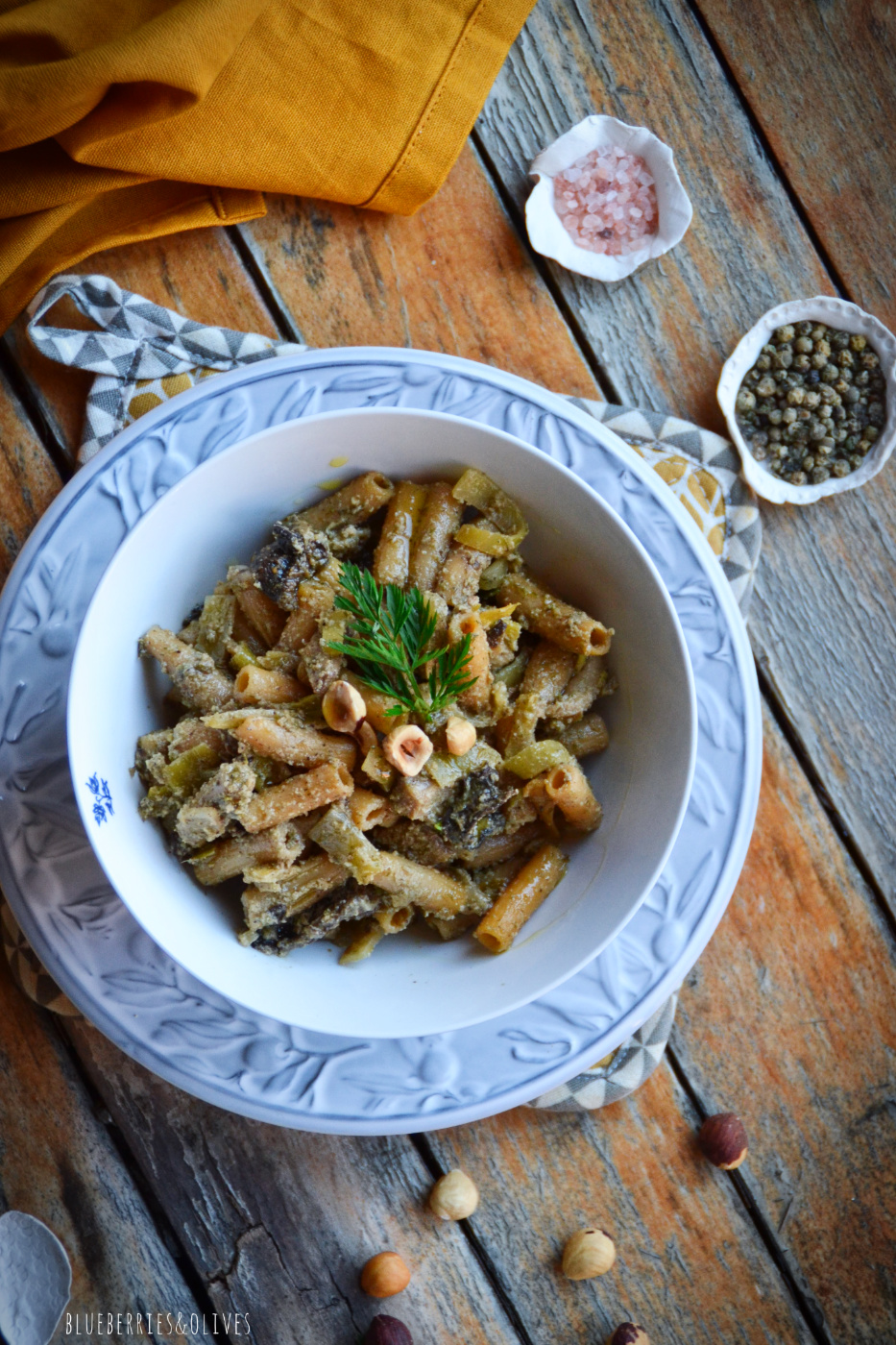 WHITE AND BLUE BOWL OF PASTA WITH FENNEL PESTO AND OLD WOODEN BACKGROUND, YELLOW TABLECLOTH