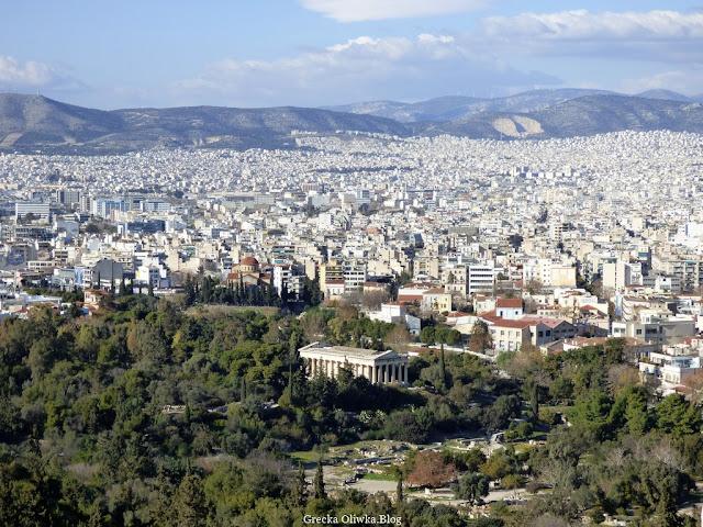widok ze wzgórza Akropolis na miliony ateńskich białych domów na zielone cedry i cisy, wzgórza i błękitne niebo