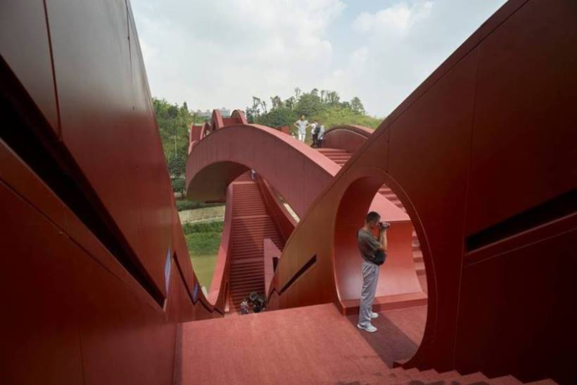 NEXT Architects, which designed the bridge, aimed in part for it to be a new public space and attraction for what is a developing area. Its was inspired by the continuously flowing Mobius ring and by Chinese knotting art