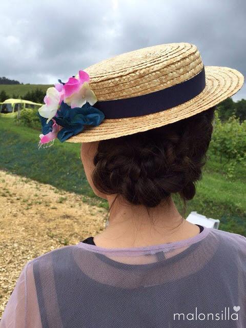 Invitada con peinado desenfadado con trenzas y recogido bajo con sombrero paja, tocado
