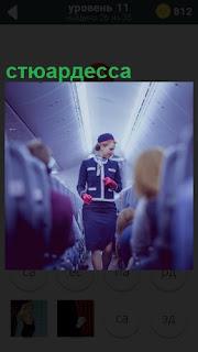 По салону самолета проходит девушка стюардесса в синем костюме