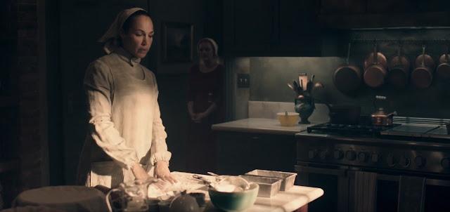 sartenes delatón, cocina de carbón, una martha vestida en tonos verdes y una criada vestida de rojo, la martha prepara pan