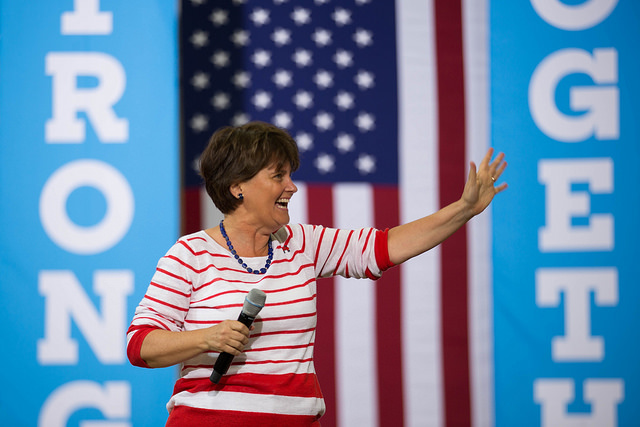 image of Anne Holton, who is married to Tim Kaine, on the campaign trail, smiling broadly and waving