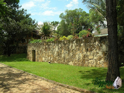 Execução do calçamento de pedra paralelepípedo em rua de pedra em sítio em Bragança Paulista-SP com os muros de pedra e o gramado com grama São Carlos.