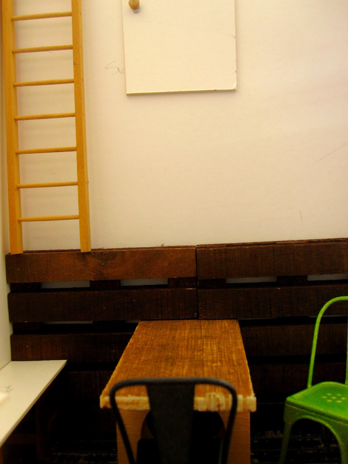 Modern dolls' house miniature half-built cafe, showing a wall with a cupboard near the ceiling and a ladder leading to it.