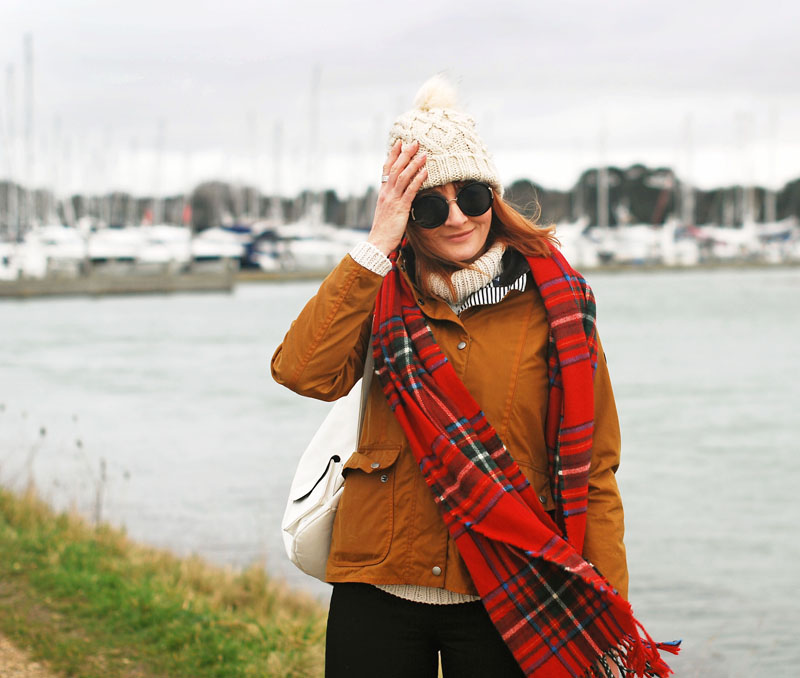 Cold weather preppy outfit for the coast: Brown Barbour jacket \ cream bobble hat and roll neck \ red tartan scarf \ black skinnies and riding boots | Not Dressed As Lamb, over 40 style blog