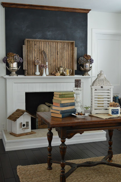 chalkboard mantel wall, gigantic wooden tray on mantel, dry hydrangeas, coffee table with stacked old books