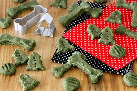 Green dog treats shaped like bones and Christmas trees on red and black polka dot napkins