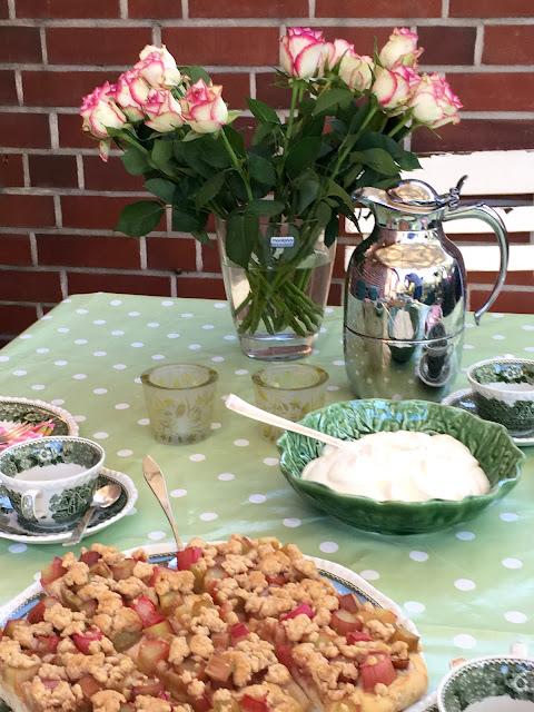 Ein herrlicher gedeckter Tisch mit Rhabarberkuchen in zartem rosé und grün