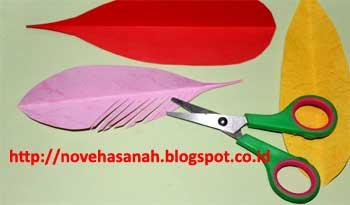mulailah pengguntingan dengan cara menyerong dan dilakukan pada salah satu sisi bentuk bulu burung imitasi yang akan dibuat